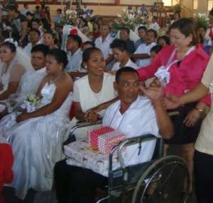 "MASS WEDDING : Mangaldan Mayor Bonafe de Vera-Parayno (extreme right) congratulates a young bride and his handicapped groom in a wheel-chair. Mayor Parayno wed 44 couples at Macario Ydia Sports Center in the tapa-producing town in February 18. ""Just stay in loved with each other,"" the simple advice given by the mayor to the spouses who used to live without the benefits of a wedlock for several years."